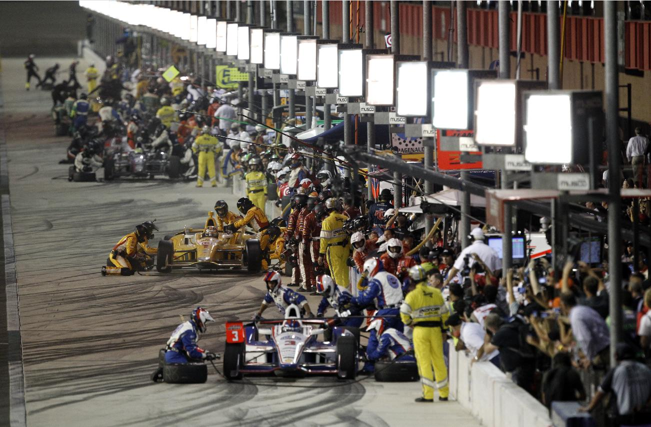 Helio Castroneves (3), of Brazil, leads several cars into pit road during the IndyCar auto race at the Auto Club Speedway, Saturday, Oct. 19, 2013, in Fontana, Calif