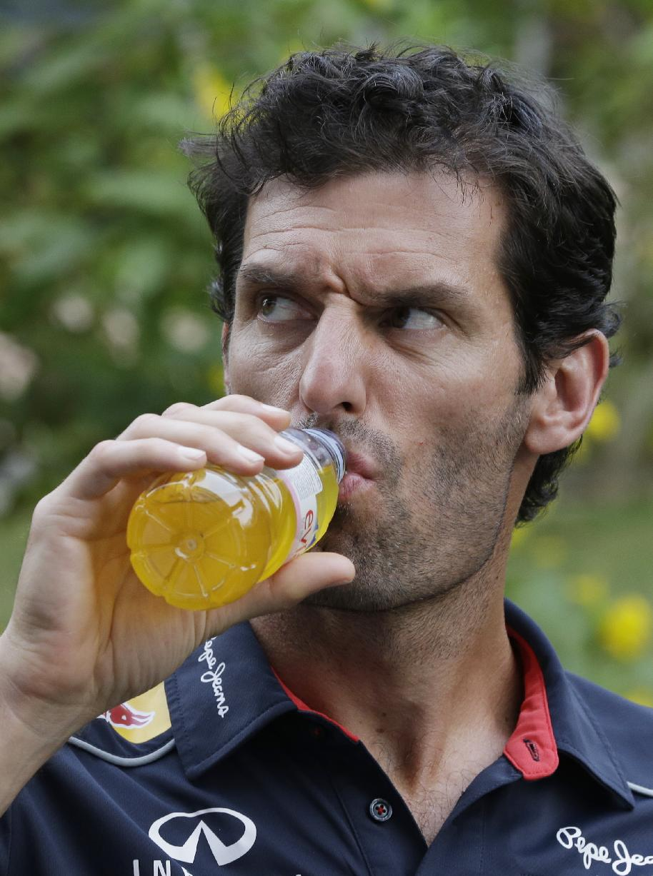 Red Bull driver Mark Webber of Australia takes a drink as he prepares for a television interview ahead of the Indian Formula One Grand Prix at the Buddh International Circuit in Noida, India, Thursday, Oct. 24, 2013