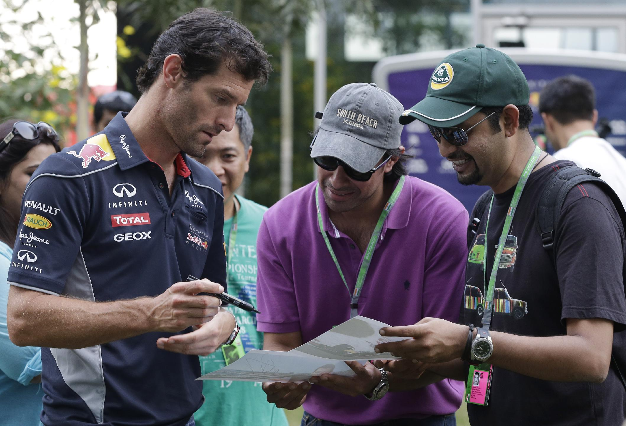 Red Bull driver Mark Webber of Australia signs his autograph for fans ahead of the Indian Formula One Grand Prix at the Buddh International Circuit in Noida, India, Thursday, Oct. 24, 2013