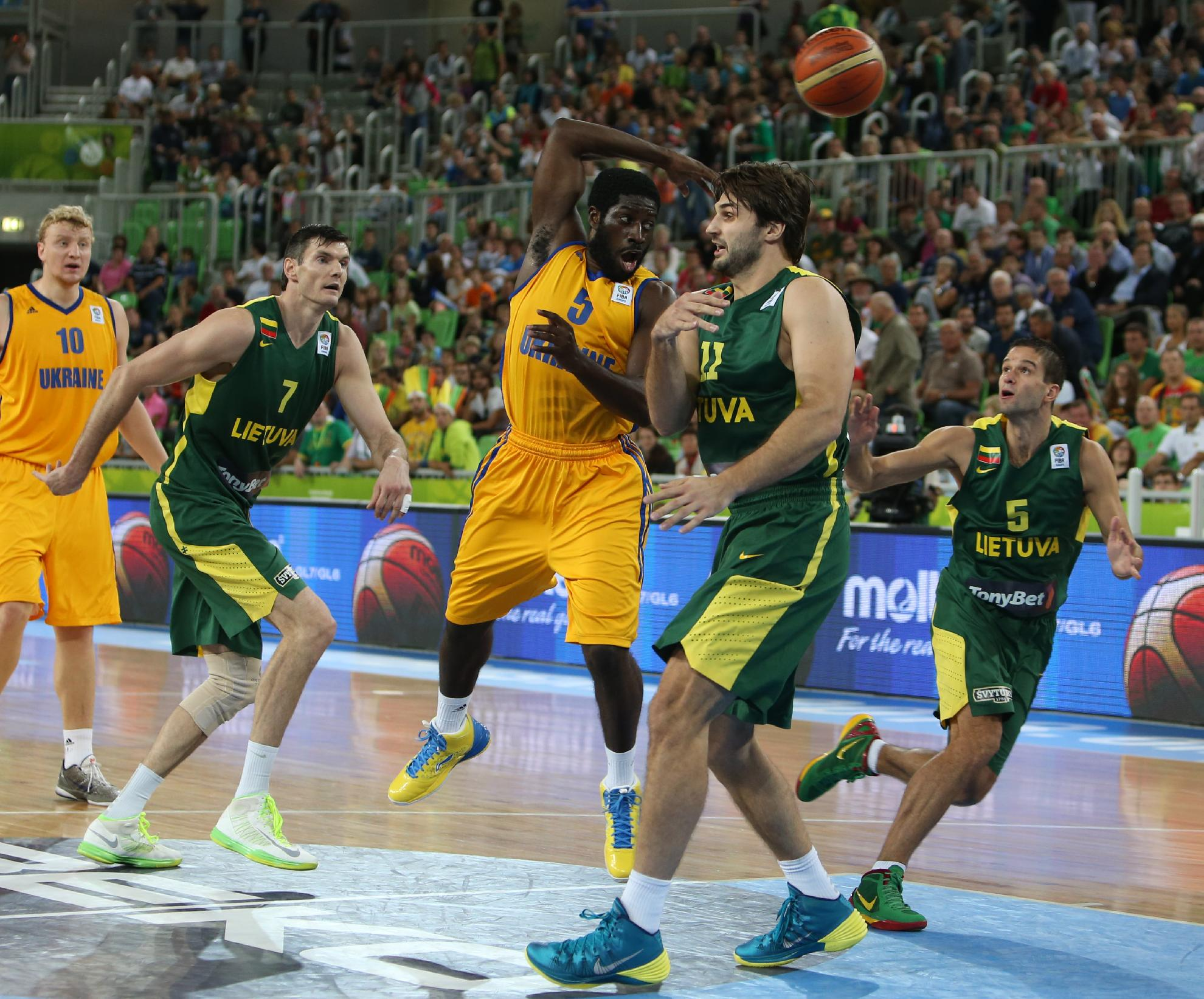 Ukraine's Eugene Jeter, center, passes the ball as Lithuania's Linas Kleiza, right, looks on during their EuroBasket European Basketball Championship Group E match at the Stozice Arena, in Ljubljana, Slovenia, Sunday, Sept. 15, 2013