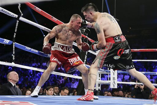 Brandon Rios lands a punch against Mike Alvarado. (AP)