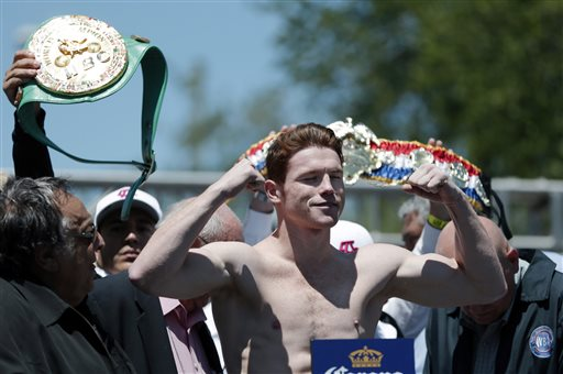 Canelo Alvarez flexes his muscles during the weigh-in for his fight against Austin Trout. (AP)