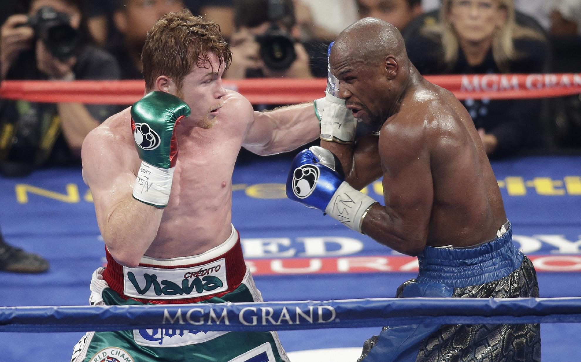 Canelo Alvarez, left, throws a punch against Floyd Mayweather Jr. during a 152-pound title fight, Saturday, Sept. 14, 2013, in Las Vegas