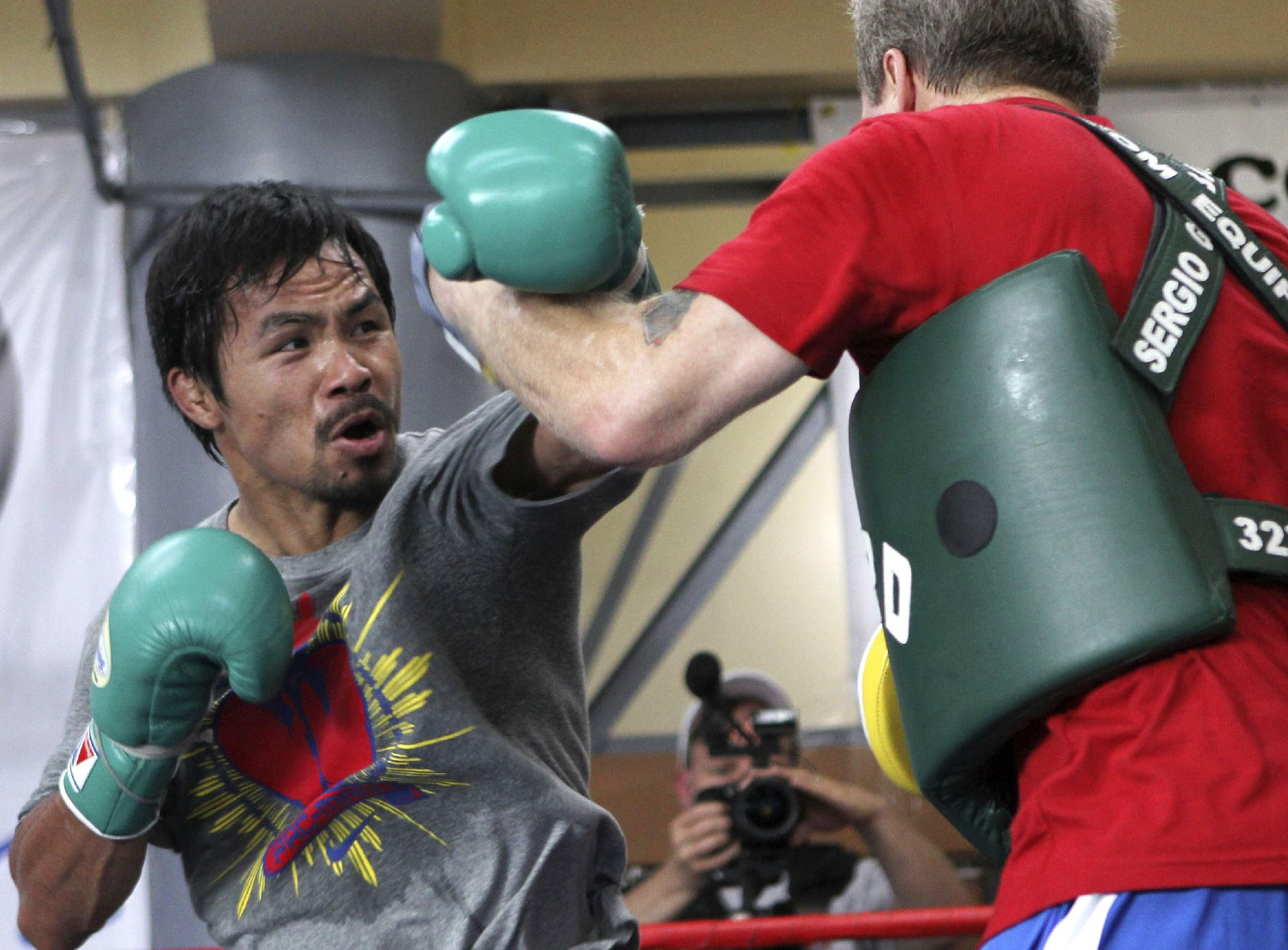 In this March 23, 2011 file photo, Filipino boxer Manny Pacquiao, left, trains with coach Freddie Roach in Baguio, northern Philippines. Pacquiao is dedicating his comeback fight against Brandon Rios to the victims of the devastating typhoon that has left hundreds of thousands displaced in his native Philippines. The eight-division champion is in camp in the southern Philippines - only about 320 kilometers (200 miles) from where Typhoon Haiyan caused the most destruction - for the Nov. 24, 2013 bout in Macau