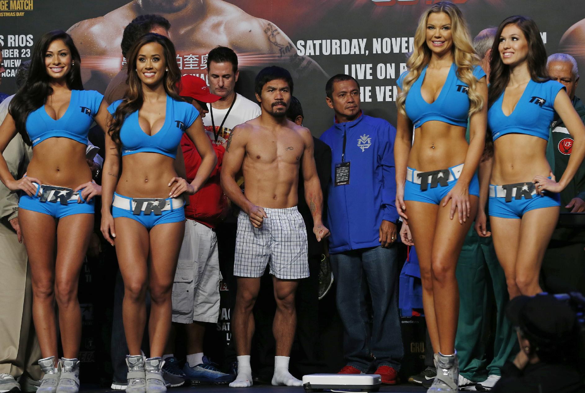Filipino boxer Manny Pacquiao, center, poses for photos during the weigh-in for his welterweight fight against Brandon Rios of the United States at the Venetian Macao in Macau Saturday, Nov. 23, 2013. Pacquiao and Rios are scheduled to fight in their welterweight boxing match at the casino on Nov. 24