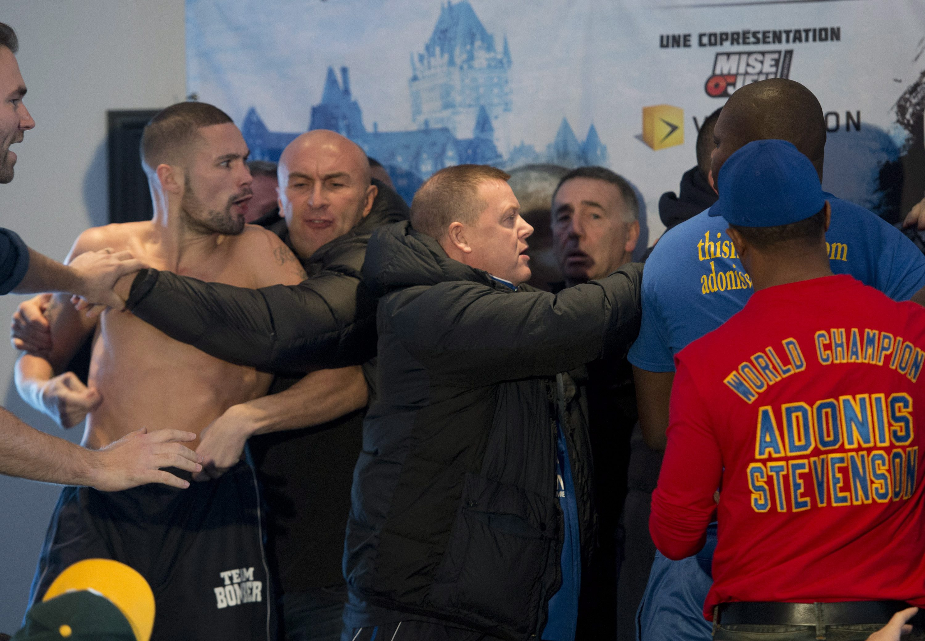 WBC light heavyweight champion Adonis Stevenson, hidden at right, and challenger Tony Bellew, left,, of England, are separated after butting heads during their weigh in Friday, Nov. 29, 2013 in Quebec City. The pair are scheduled to step in to the ring on Saturday, for Stevenson's WBC title