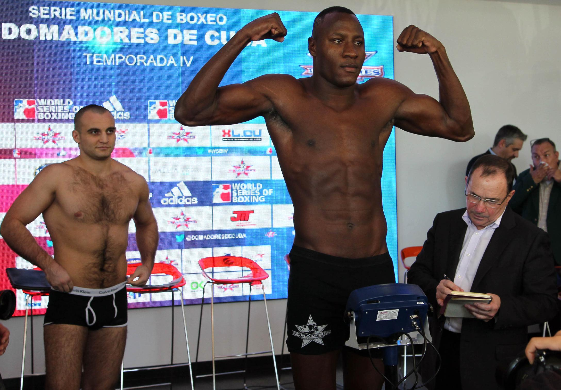 CORRECTS DAY OF BOXING MATCHES Cuban heavyweight boxer Erislandy Savon, at front right, poses for photos during the weigh-in session as his opponent Vitaly Kudukhov from Russia, left, looks on in  Havana, Cuba, Thursday, Dec. 5, 2013. Cuban and Russian boxers will face-off at a World Series of Boxing (WSB) event Friday