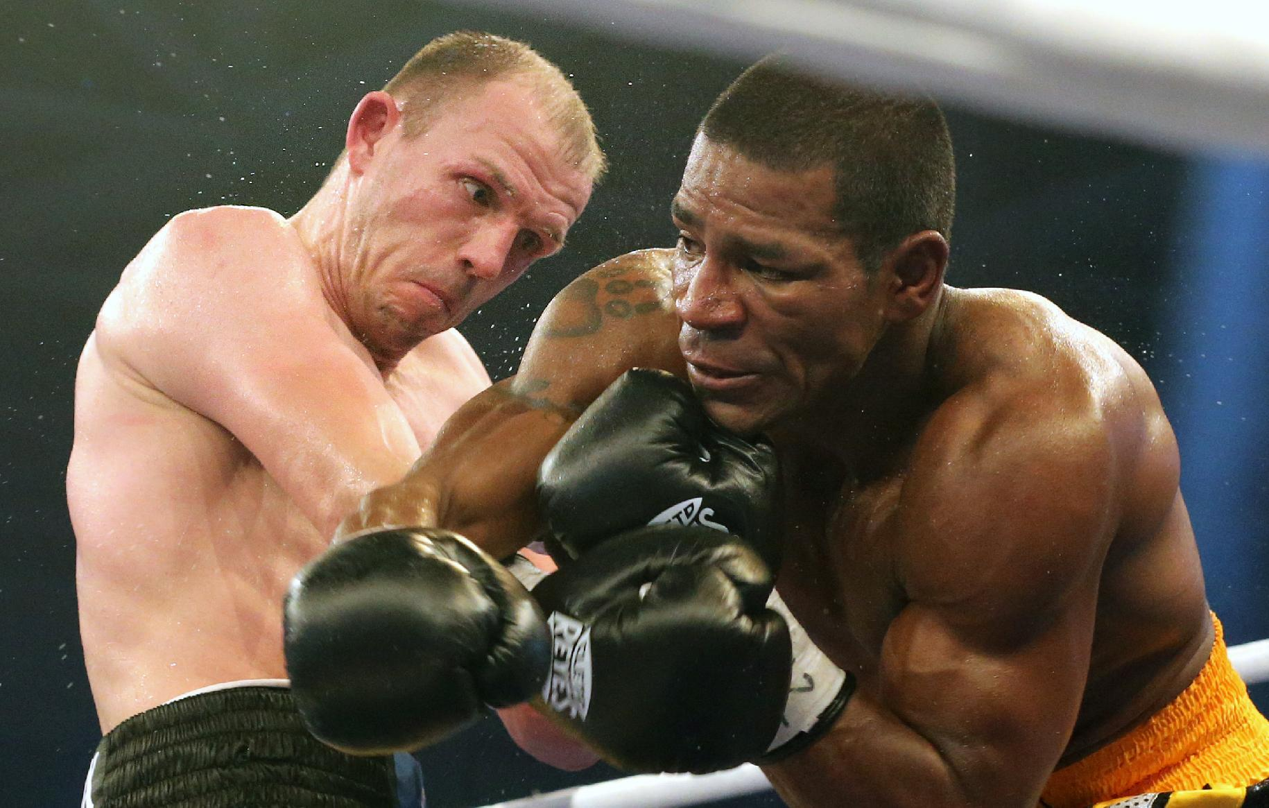 In this picture taken Saturday evening Dec. 14, 2013, German boxer Juergen Braehmer, left,  punches  US Marcus Oliveira  during their title bout in Neubrandenburg, eastern Germany.  Germany's Juergen Braehmer defeated Marcus Oliveira by unanimous decision to take the vacant WBA world light heavyweight title on Saturday night. The judges scored it  in favor of the 35-year-old Braehmer, a former WBO champion, who withstood a late barrage from the previously undefeated American in the last round to claim his second world title. The title had been vacant since Kazakhstan's Beibut Shumenov was declared the WBA's
