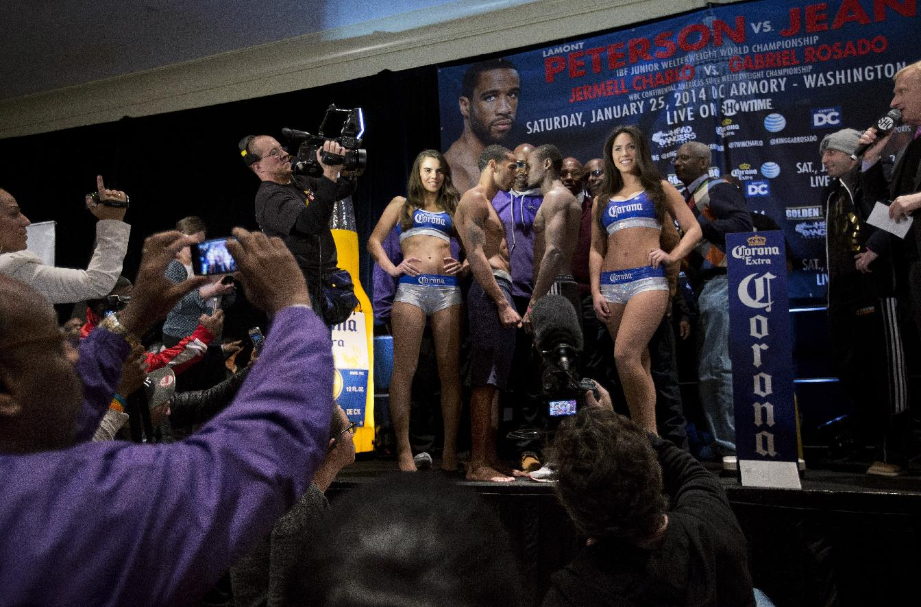 IBF junior welterweight champion Lamont Peterson, center left, and Canadian Dierry Jean, center right, pose for photographers during the official weigh-in, Friday, Jan. 24, 2014, in Washington, for the their Saturday bout at the DC Armory in Washington