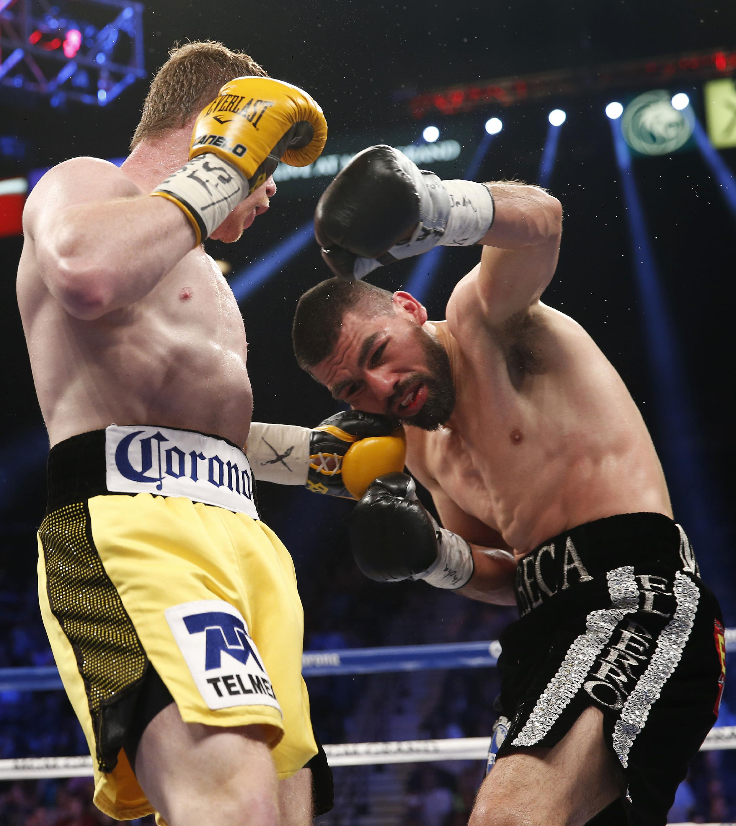 Saul Alvarez of Guadalajara Mexico, left, trades punches with Alfredo Angulo of Mexicali Mexico during their super welterweight boxing match, Saturday, March 8, 2014, at The MGM Grand Garden Arena in Las Vegas. Alvarez won by TKO when the fight was stopped by referee Tony Weeks