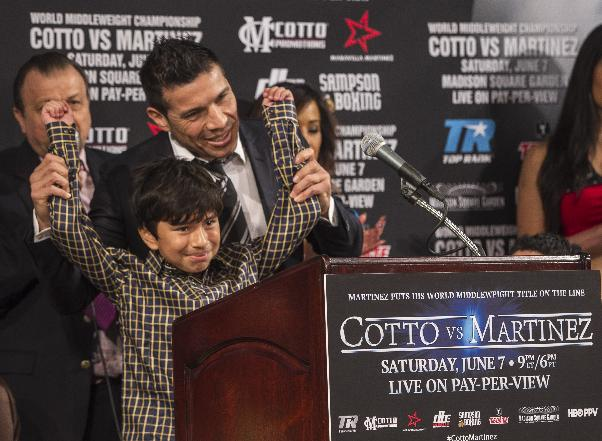 WBC middleweight champion Sergio Martinez, right, of Argentina, lifts the arms of a young bullying victim, Nicolas Perez, as he dedicates his fight against challenger boxer Miguel Cotto, of Puerto Rico to victims of  bullying during a news conference in Beverly Hills, Calif., Wednesday, Mar. 12, 2014. Cotto and Martinez will face in a World Middleweight Championship bout scheduled June 7, in New York's Madison Square Garden
