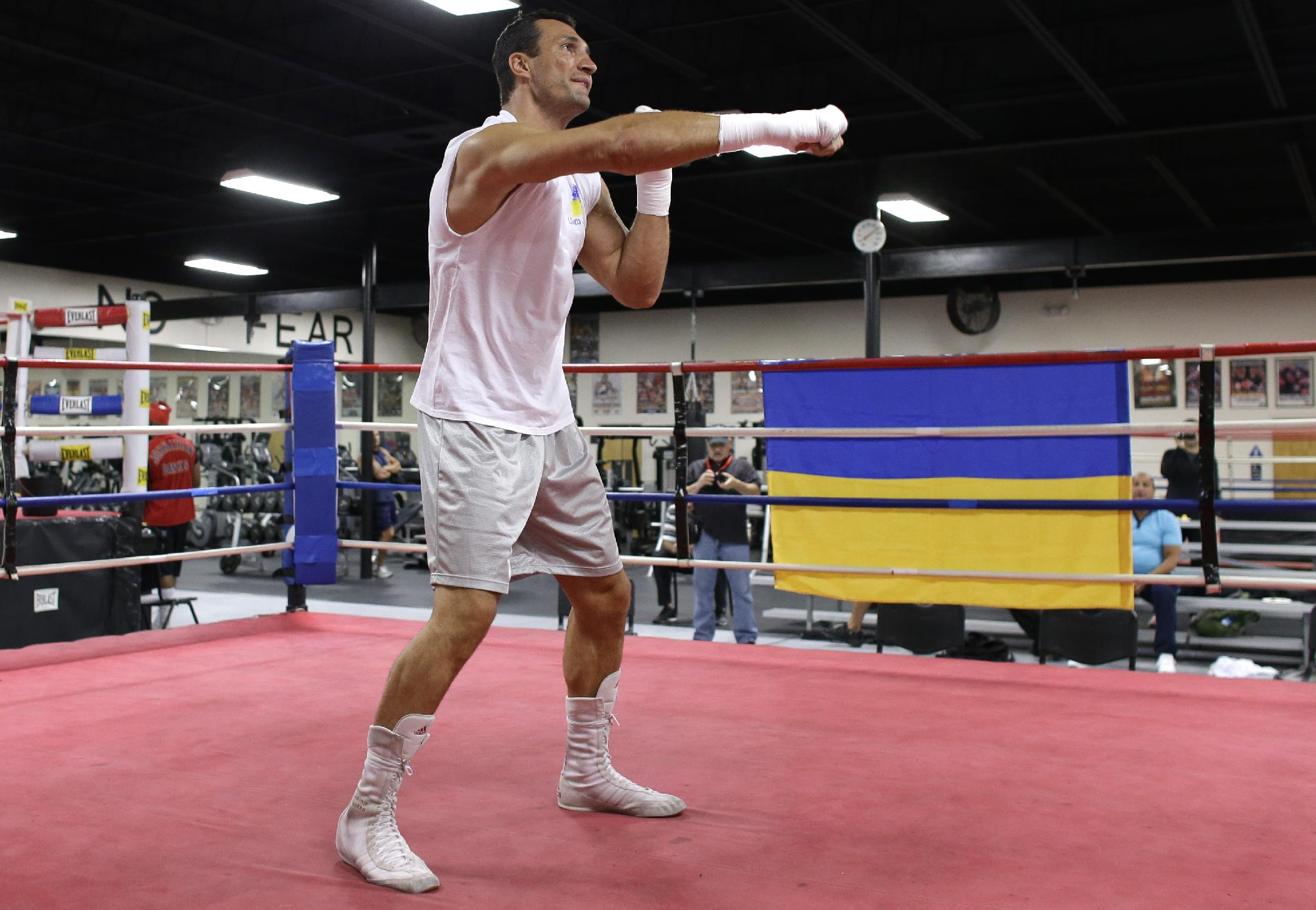 Undefeated World Heavyweight Boxing Champion Wladimir Klitschko, of Ukraine, trains at the Lucky Street Boxing Gym, Thursday, March 20, 2014, in Hollywood, Fla. Klitschko is preparing for his upcoming fight April 26 against Alex Leapai in Germany. The Ukrainian flag hangs on the ring