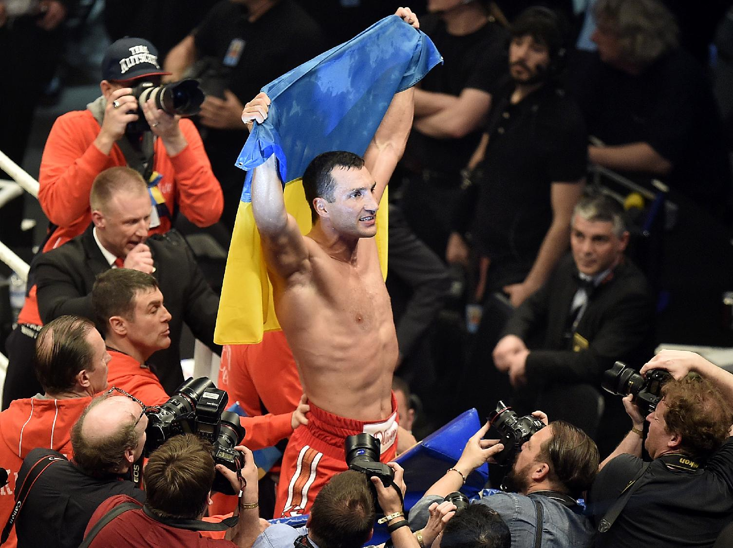 World boxing champion Wladimir Klitschko celebrates with the Ukrainian flag after defeating Samoan-born Australian challenger Alex Leapai following their IBF, IBO, WBO and WBA heavyweight title bout in Oberhausen, Germany, Saturday, April 26, 2014. Klitschko won the fight by technical knock out in the fifth round