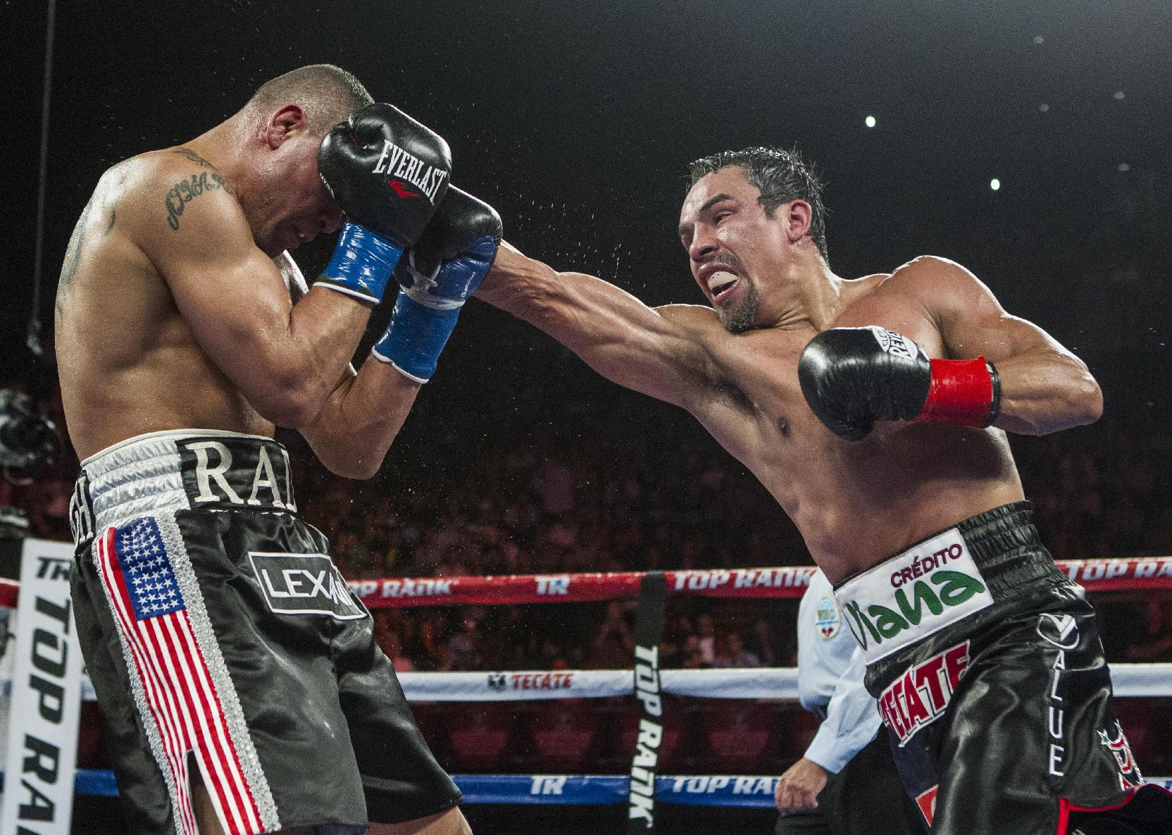Juan Manuel Mrquez, right, of Mexico, lands a punch against Mike Alvarado in the fifth round of a WBO welterweight title boxing match at the Forum in Inglewood, Calif., Saturday, May 17, 2014. Mrquez won the title