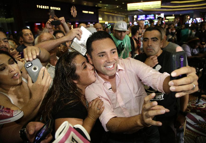 Boxer Oscar De La Hoya poses for photographs with fans during a media workout Wednesday, July 9, 2014, in Las Vegas. De La Hoya was attending a media workout for a boxing fight between Canelo Alvarez and Erislandy Lara