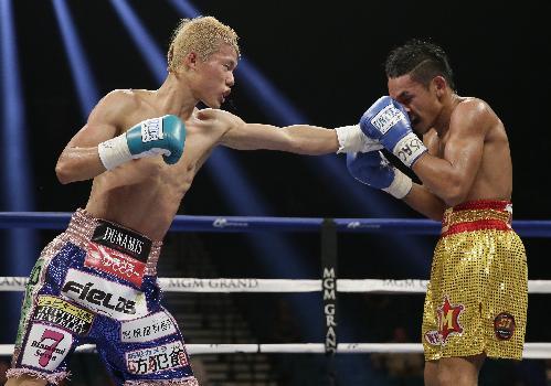 Tomoki Kameda, of Japan, lands a punch on Pungluang Singyu, right, during their WBO bantamweight title fight,  Saturday, July 12, 2014, in Las Vegas