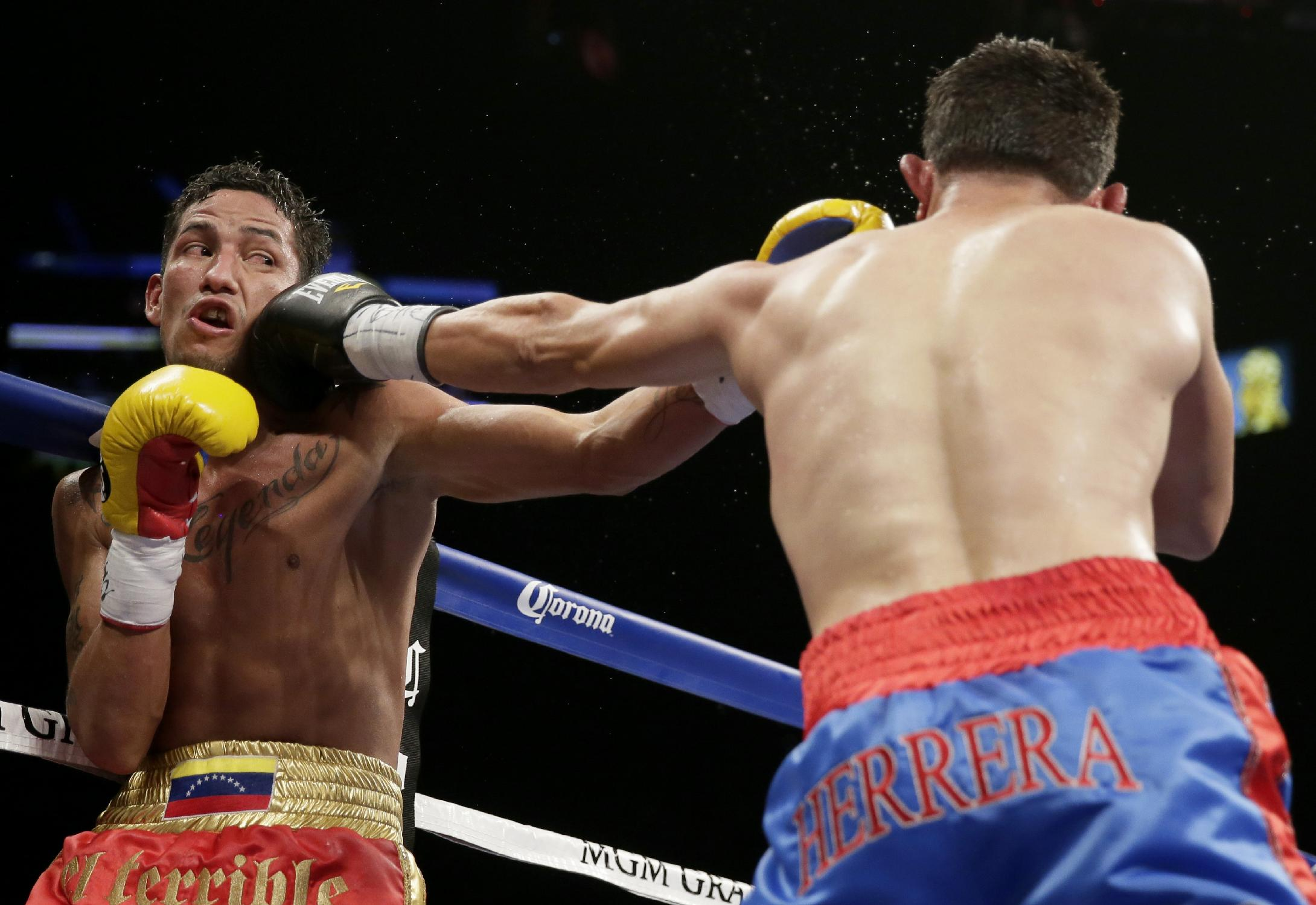 Johan Perez, left, takes a hit from Mauricio Herrera during their WBA super lightweight title fight, Saturday, July 12, 2014, in Las Vegas