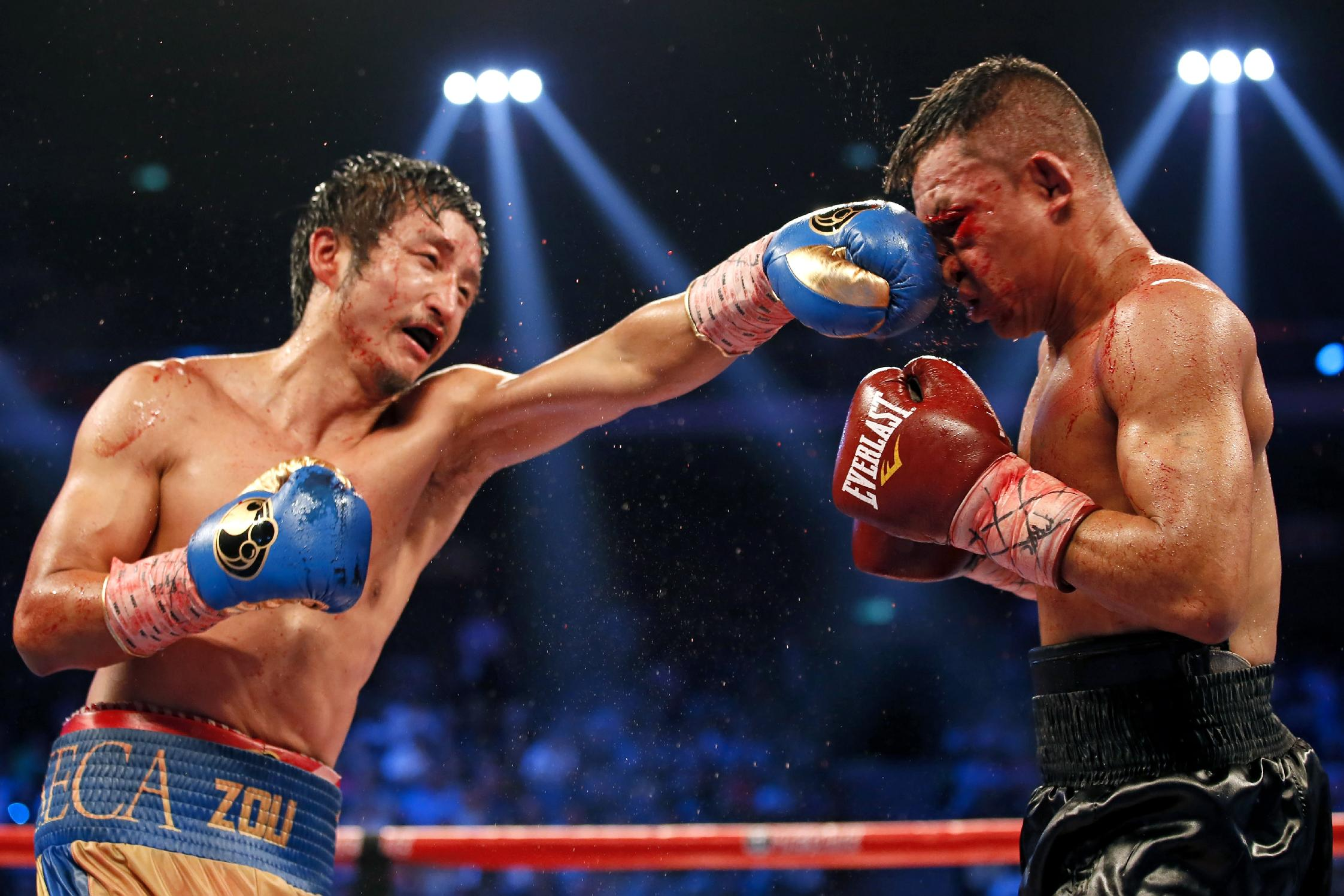 Chinese boxer Zou Shiming, left, delivers a punch to Colombian boxer Luis De La Rosa during the WBO international flyweight title match in Macau, China, Saturday, July 19, 2014. Zou Shiming won the competition