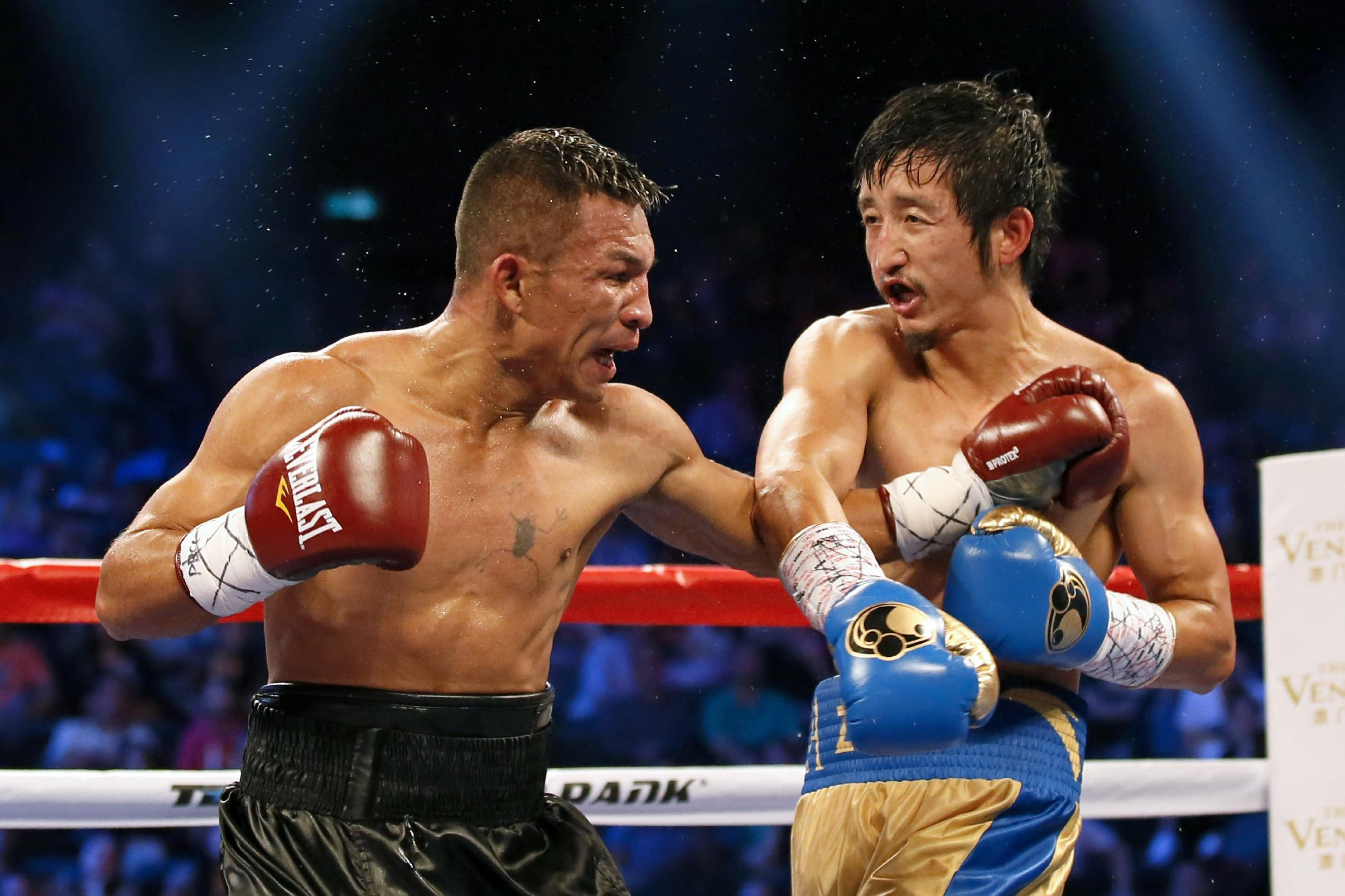 Chinese boxer Zou Shiming, right, fights with Colombian boxer Luis De La Rosa during the WBO international flyweight title match in Macau, China, Saturday July 19, 2014. Zou Shiming won the competition