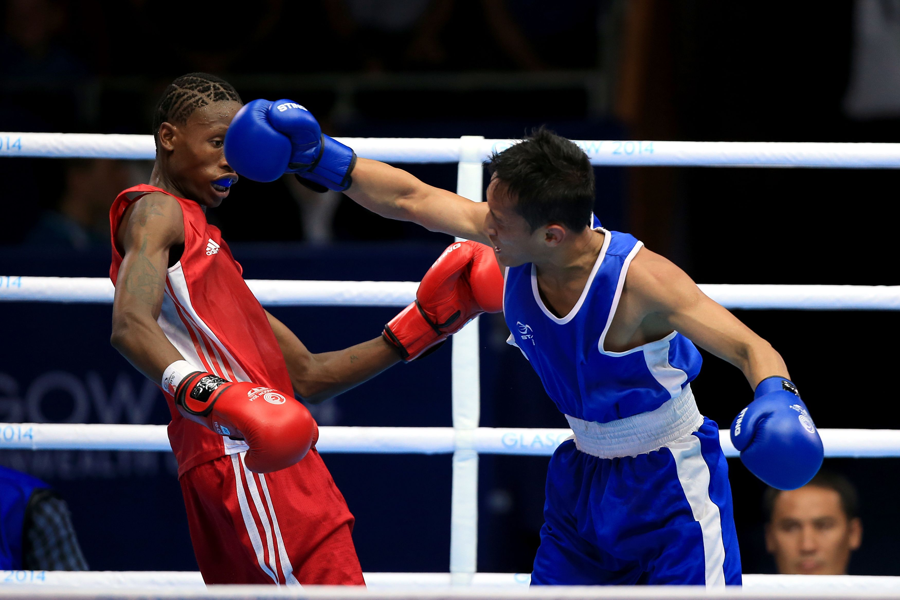 Lesotho's Inululeko Suntele, left, in action against Malaysia's Muhamad Fuad Mohd Redzuan in the Men's Light Fly round of 32 match at the SECC during the 2014 Commonwealth Games in Glasgow, Scotland, Saturday, July 26, 2014