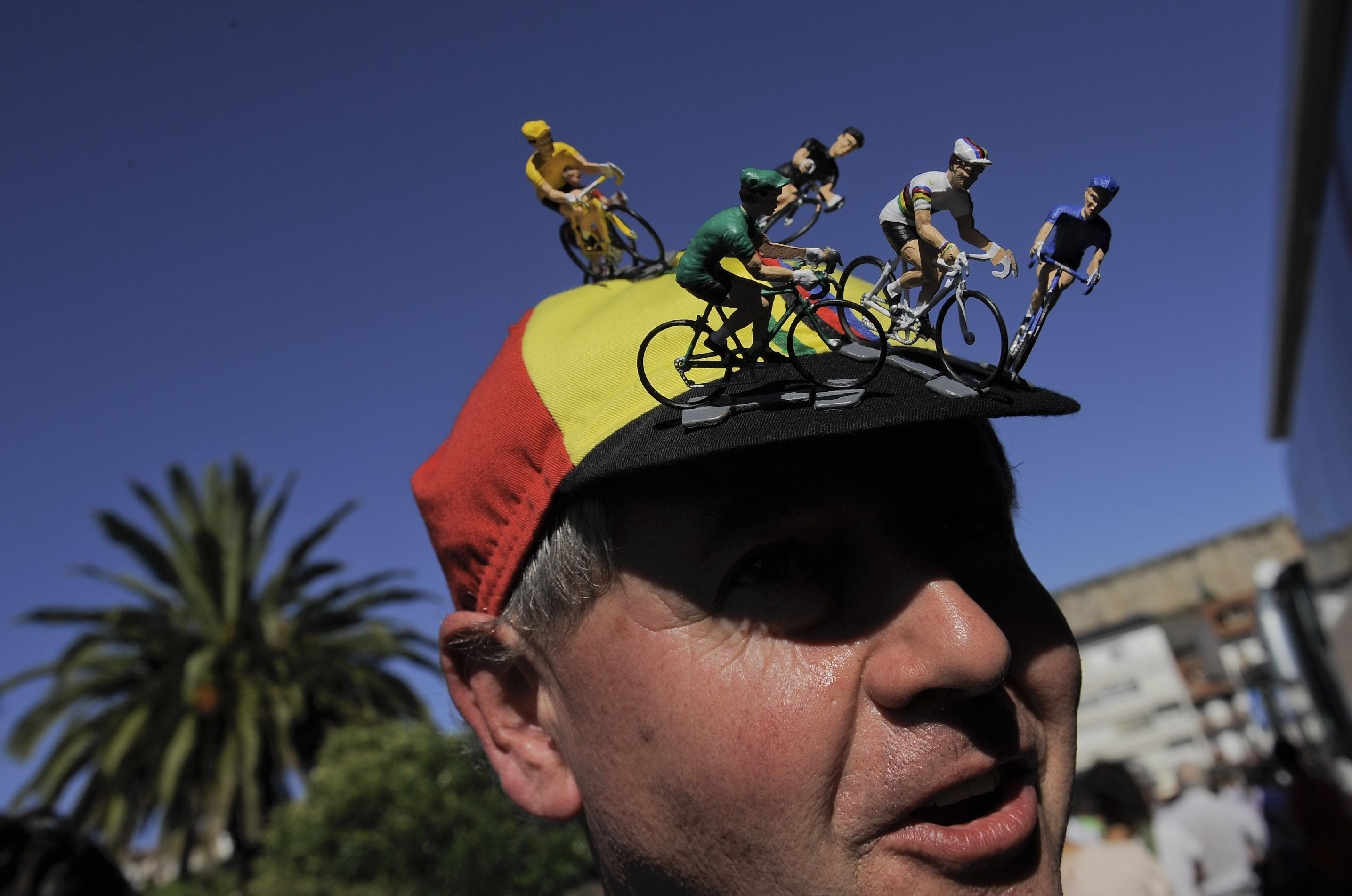 A spectator of the Spanish La Vuelta cycling race, wearing on his cap toy cyclists, before the start of the 19th stage of the  race, a 181-kilometer (112.5-mile) leg between San Vicente de La Barquera and Oviedo, in San Vicente de La Barquera, northern Spain, Friday, Sept. 13, 2013