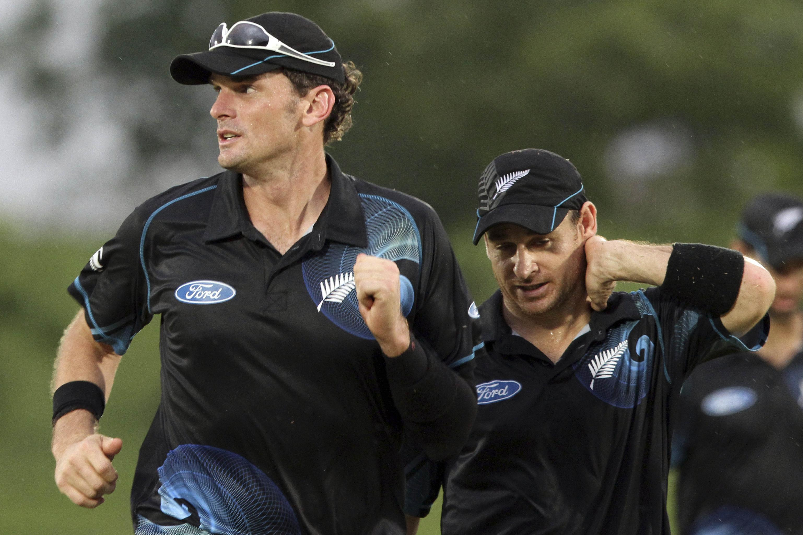 New Zealand's captain Kyle Mills, left, and Nathan McCullum leave the ground as lightning interrupts the second one-day international cricket match between Sri Lanka and New Zealand in Sooriyawewa, Sri Lanka, Tuesday, Nov. 12, 2013. (AP Photo)