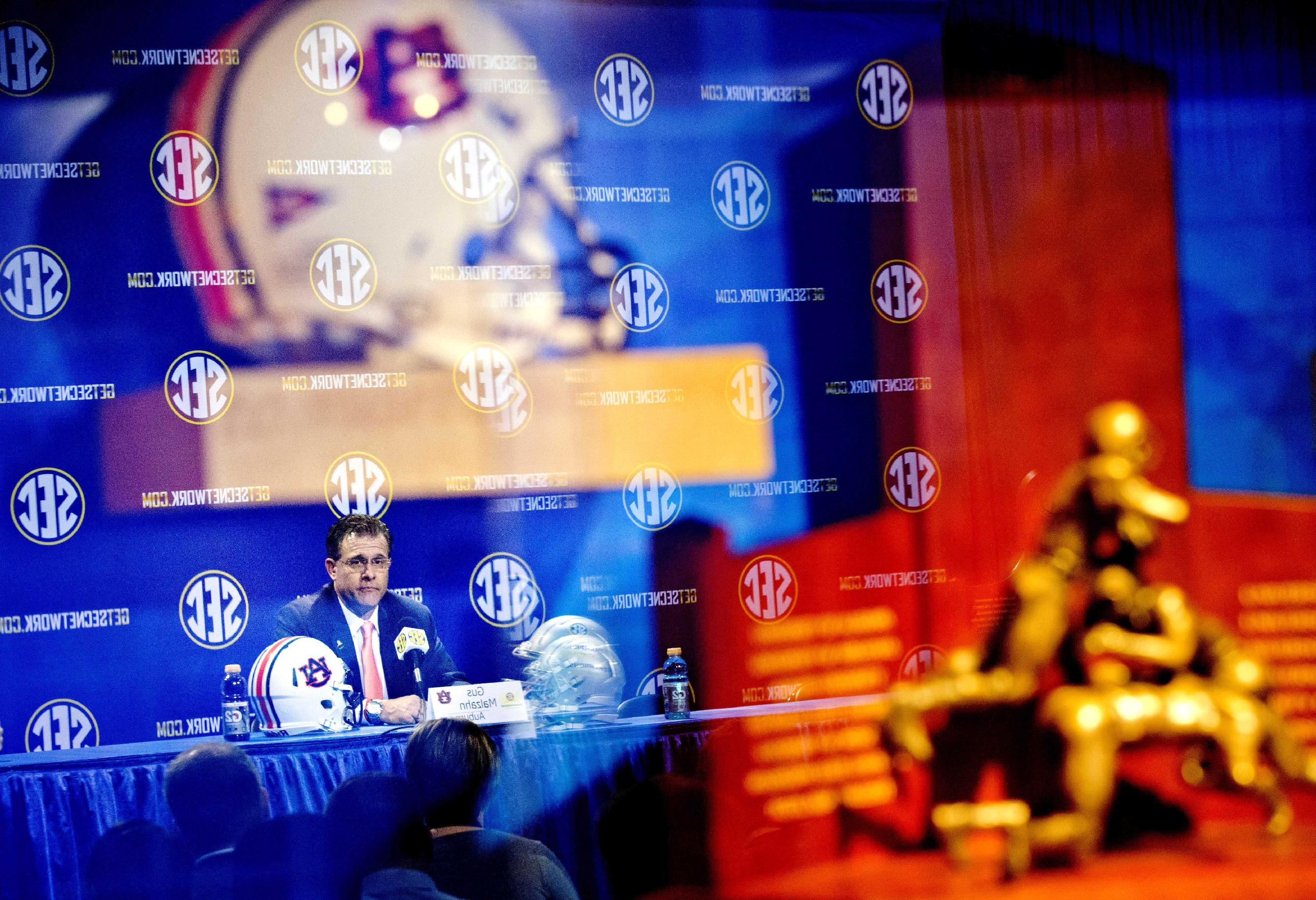 Auburn head coach Gus Malzahn is reflected in a glass case showcasing his team's helmet, top left, and the Southeastern Conference championship trophy at right, as he pauses while speaking at a press conference ahead of Saturday's SEC championship college football game against Missouri, Friday, Dec. 6, 2013, in Atlanta
