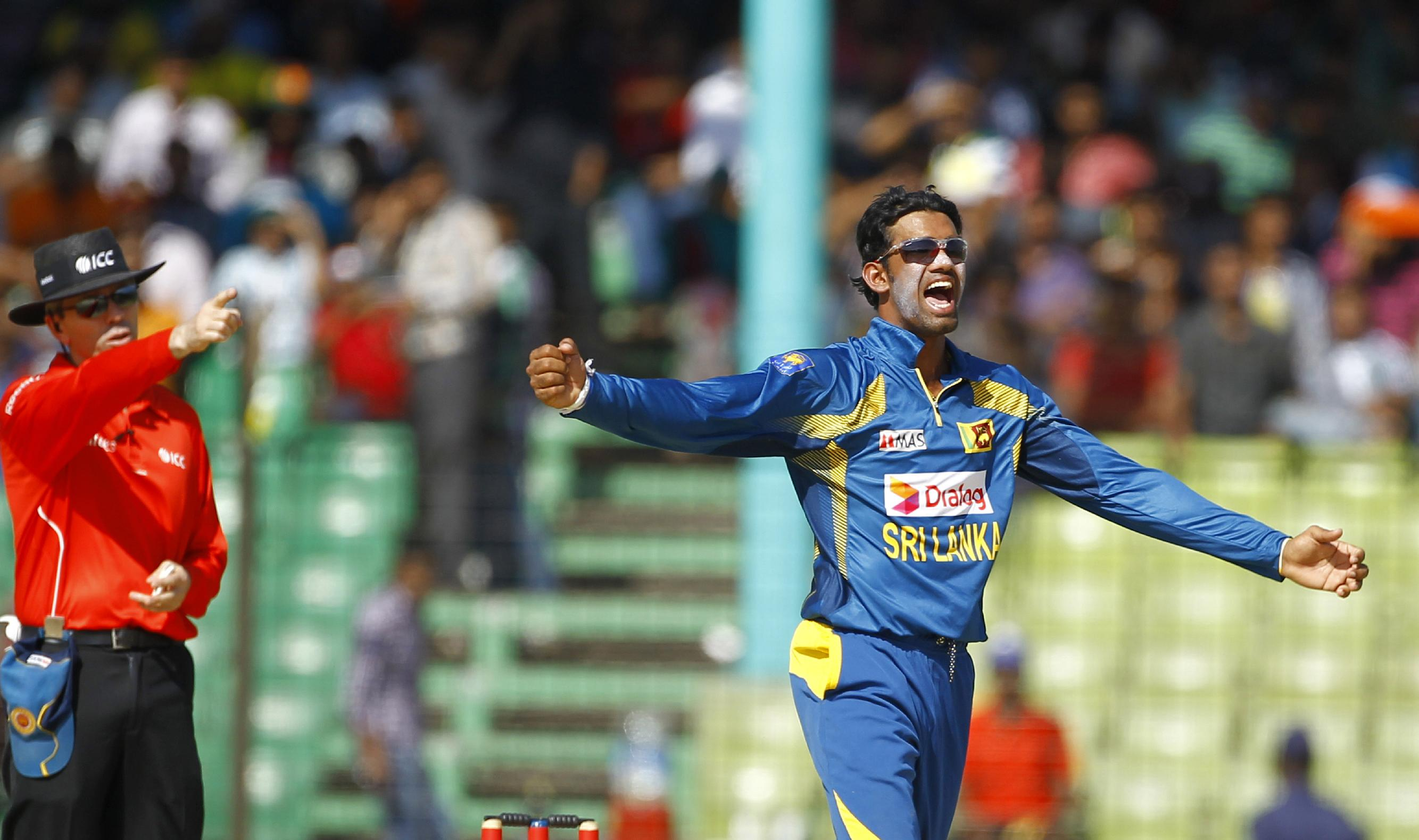 Sri Lanka's Sachithra Senanayake, right, celebrates the wicket of India's Rohit Sharma, unseen, during the Asia Cup one-day international cricket tournament, in Fatullah, near Dhaka, Bangladesh, Friday, Feb. 28, 2014