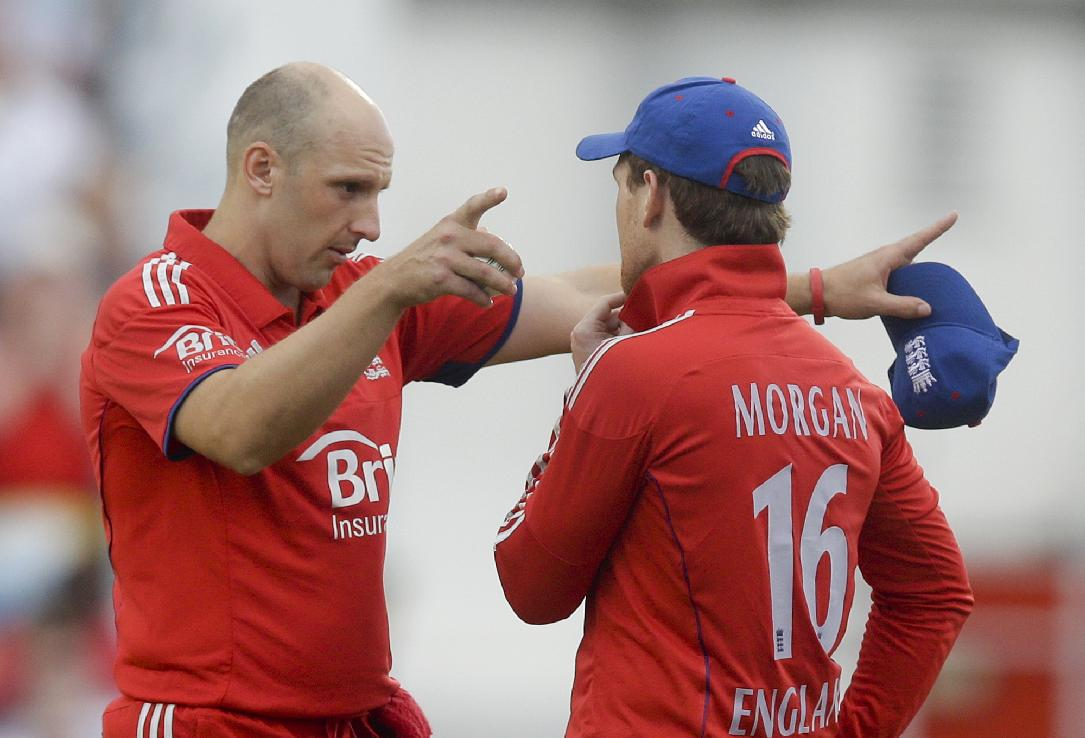 England's James Tredwell talks to Eoin Morgan during the second T20 International cricket match against West Indies at the Kensington Oval in Bridgetown, Barbados, Tuesday, March 11, 2014