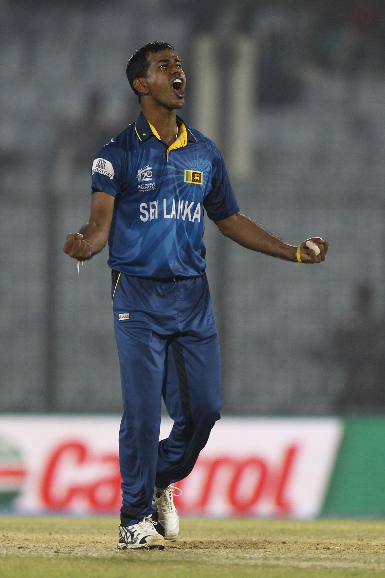 Sri Lanka's Nuwan Kulasekara celebrates the dismissal of England's Jos Buttler during their ICC Twenty20 Cricket World Cup match in Chittagong, Bangladesh, Thursday, March 27, 2014