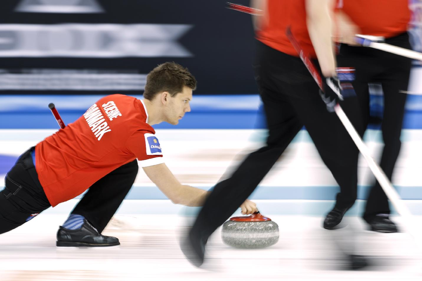 Denmark's Rasmus Stjerne releases the stone during a match against Norway at the World Men's Curling Championship at the Capital Gymnasium in Beijing, China, Sunday, March 30, 2014