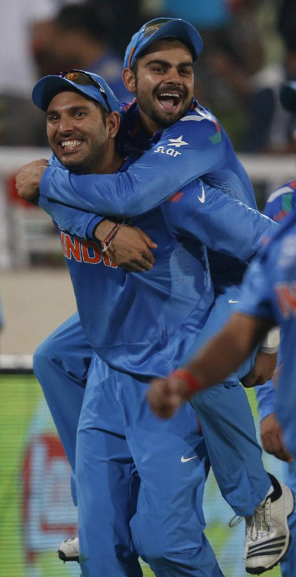 India's Yuvraj Singh, left, carries teammate Virat Kohli on his back as they celebrate their win over Australia in their ICC Twenty20 Cricket World Cup match in Dhaka, Bangladesh, Sunday, March 30, 2014. India won the match by 73 runs