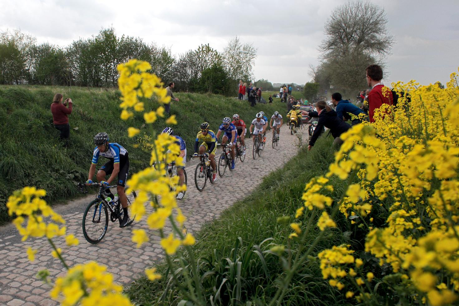 Riders steer their bikes on a cobblestone-paved section during the 112th edition of the Paris-Roubaix cycling classic, a 257 kilometer (159,69 mile) one day race, of which 51,1 kilometers (31,7 miles) are run on cobblestones, at the velodrome in Roubaix, northern France, on Sunday, April 13, 2014