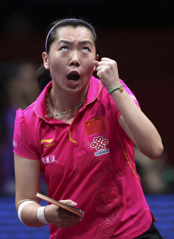 Li Xiaoxia of China reacts after winning a point against Singapore's Feng Tianwei during their semifinal match of the World Team Table Tennis Championships in Tokyo, Sunday, May 4, 2014