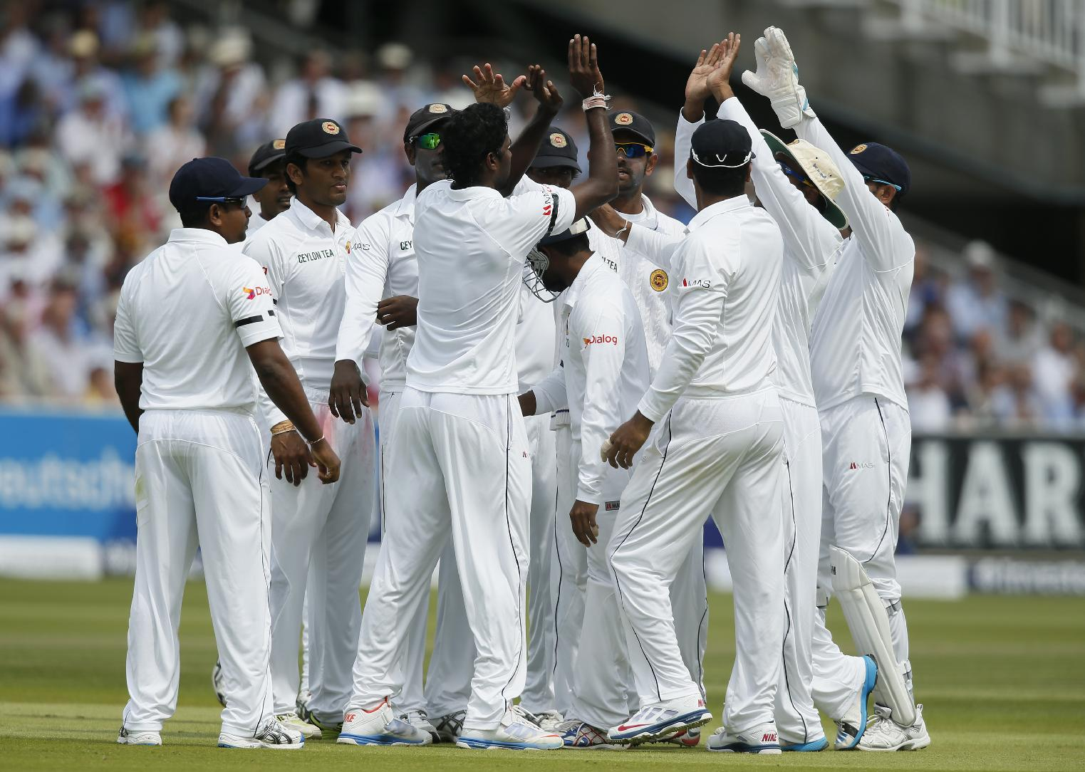 Sri Lanka's Kaushal Silva, at center, is congratulated by teammates after taking a catch to dismiss England's Matt Prior on the second day of the first test cricket match between England and Sri Lanka at Lord's cricket ground in London, Friday June 13, 2014