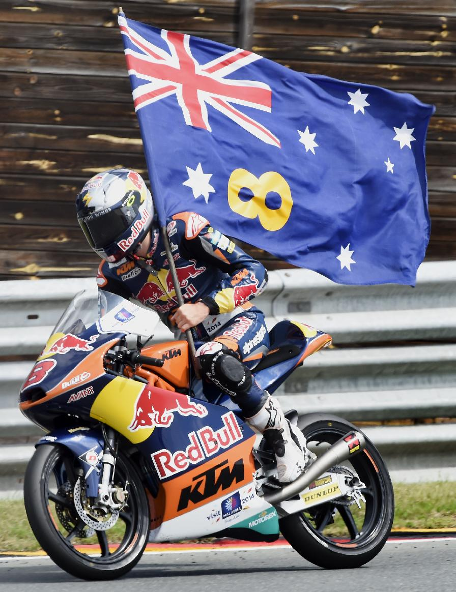First placed Jack Miller from Australia holds a flag after the Moto3 race at the Sachsenring circuit in Hohenstein-Ernstthal, Germany, Sunday, July 13, 2014