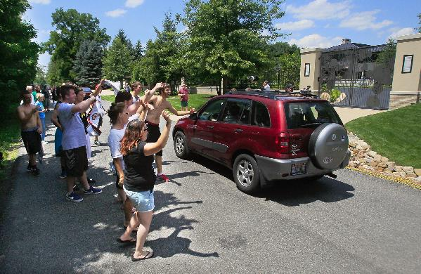 In this July 11, 2014 file photo, Cleveland Cavaliers basketball fans celebrate in front of the house of LeBron James, in Bath, Ohio, after learning of James' decision to sign as a free-agent with the Cavaliers. LeBron James sent cupcakes to his neighbors, Tuesday, July 22, 2014, according to multiple media outlets, to apologize for the ruckus caused by the announcement of his homecoming earlier this month