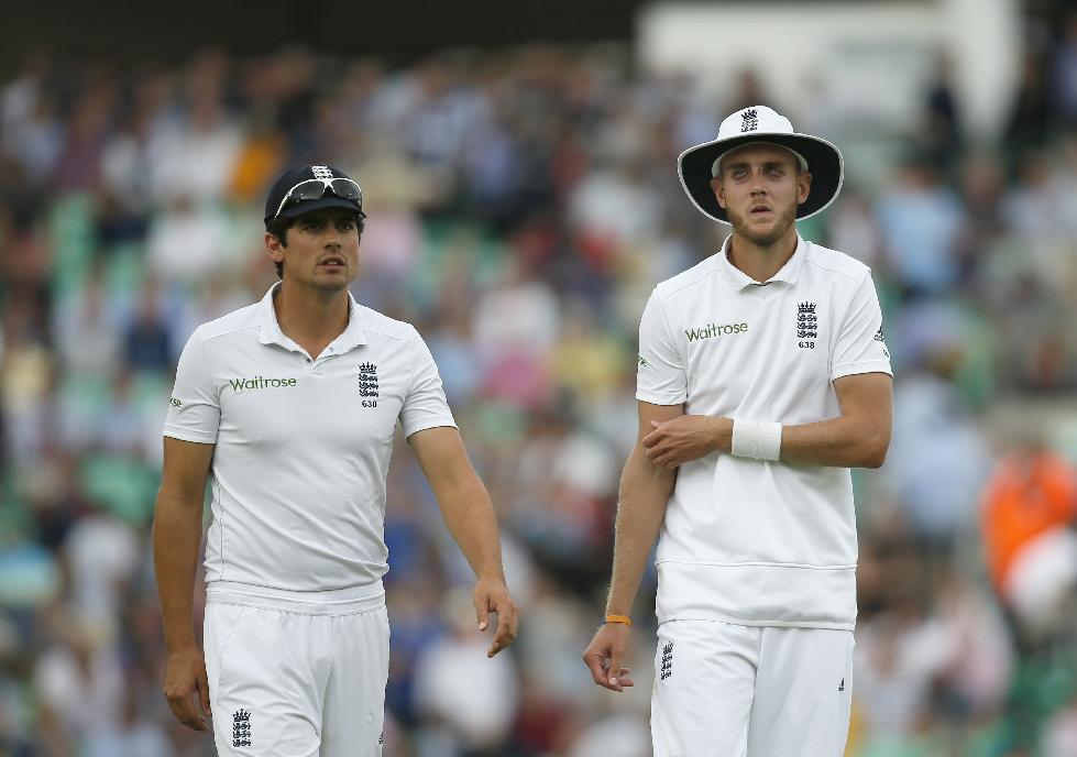 England's Stuart Broad, right, talks to captain Alastair Cook as they walk off for the tea interval during the first day of the fifth test cricket match against India at Oval cricket ground in London, Friday, Aug. 15, 2014