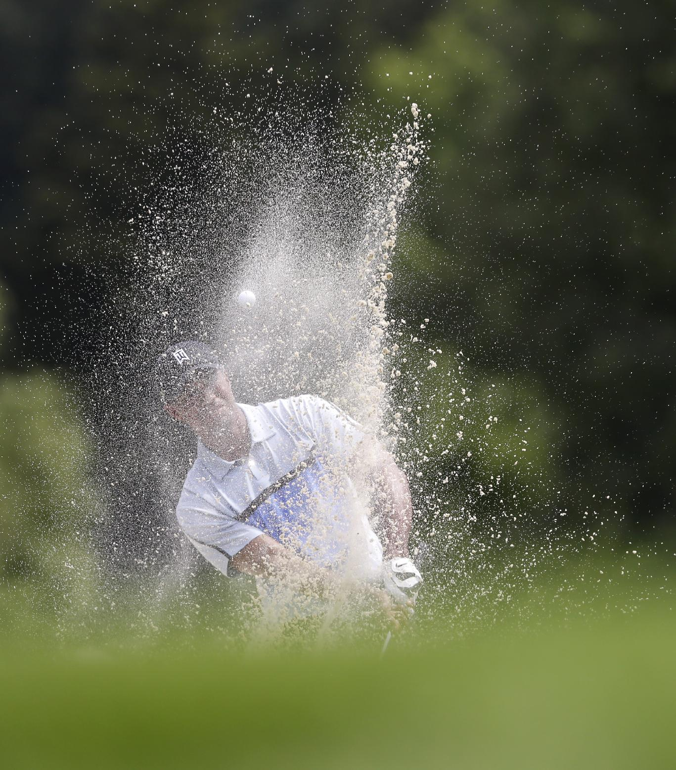 Tiger Woods hits his second shot out of a bunker on the ninth hole, his last of Round 1. (AP)