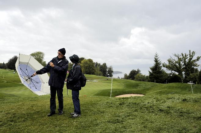 Supporters wait during a rain delay in the first round of the Evian Championship women's golf tournament in Evian, eastern France, Thursday, Sept. 12, 2013