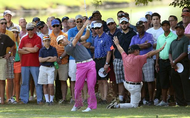 Near spectators, Sergio Garcia, center,  follows through on his second shot on the first fairway during round one of the 2013 Tour Championship golf tournament at East Lake Golf Club, Thursday, Sept. 19, 2013, in Atlanta. Garcia finished tied for sixth with a round of 2 under par