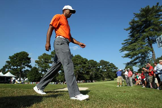 Tiger Woods walks off of the 14th green during round one of the 2013 Tour Championship golf tournament at East Lake Golf Club, Thursday, Sept. 19, 2013, in Atlanta. Woods finished in 29th place with a round of 3 over par