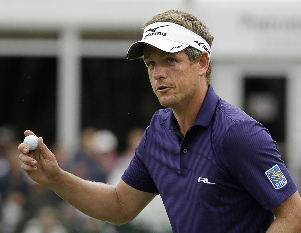 Luke Donald, of England, acknowledges the applause of the gallery after sinking a putt on the 16th hole during the third round of play in the Tour Championship golf tournament at East Lake Golf Club, in Atlanta, Saturday, Sept. 21, 2013