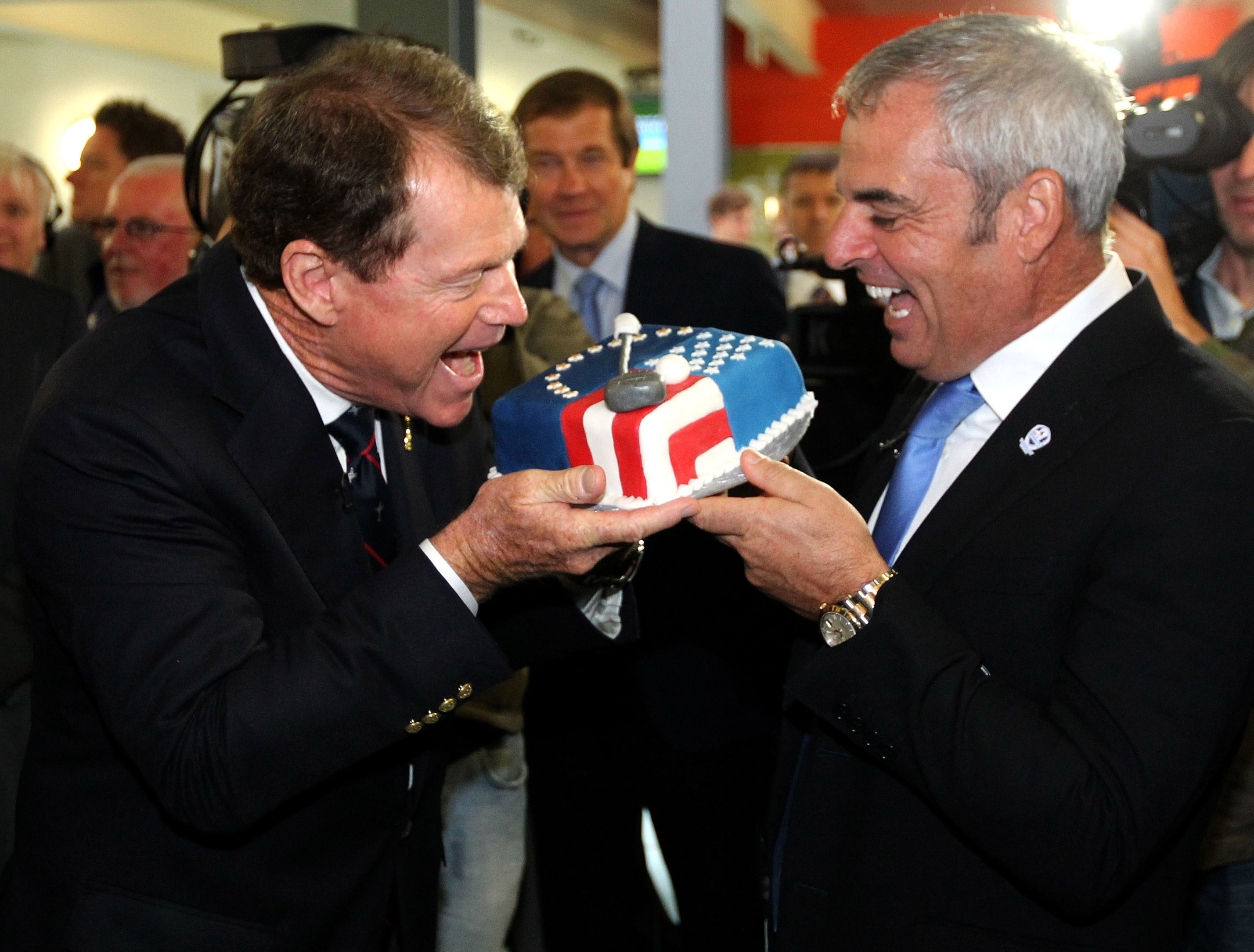 European Ryder Cup Captain Paul McGinley, right, and US Ryder Cup Captain Tom Watson, pretend to eat a cake covered in icing to represent their teams' flags, during a visit to Auchterarder Primary School, Perthshire,  Scotland, in Scotland, Tuesday Sept. 24, 2013