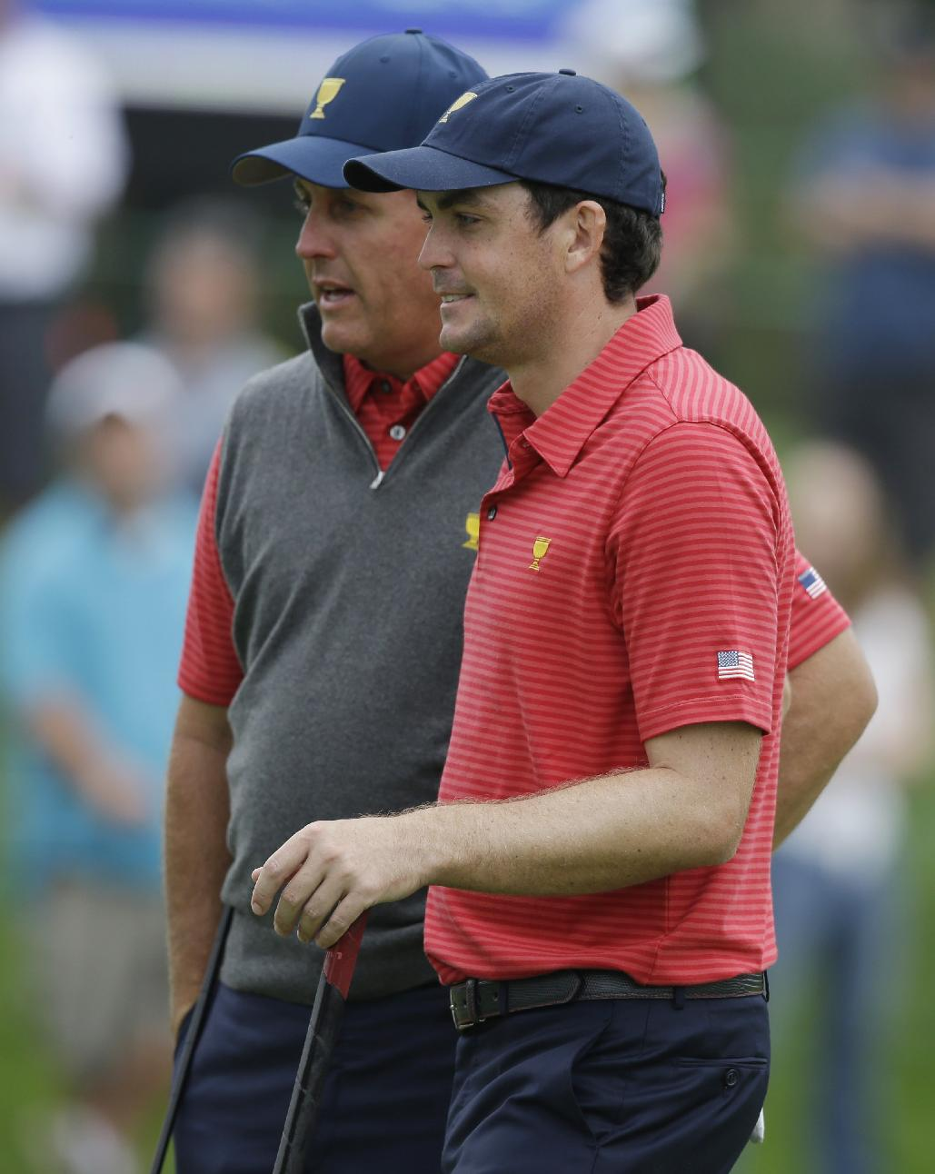 United States team player  Phil Mickelson, left, talks with teammate Keegan Bradley on the 10th green during a practice round for the Presidents Cup golf tournament at Muirfield Village Golf Club Wednesday, Oct. 2, 2013, in Dublin, Ohio