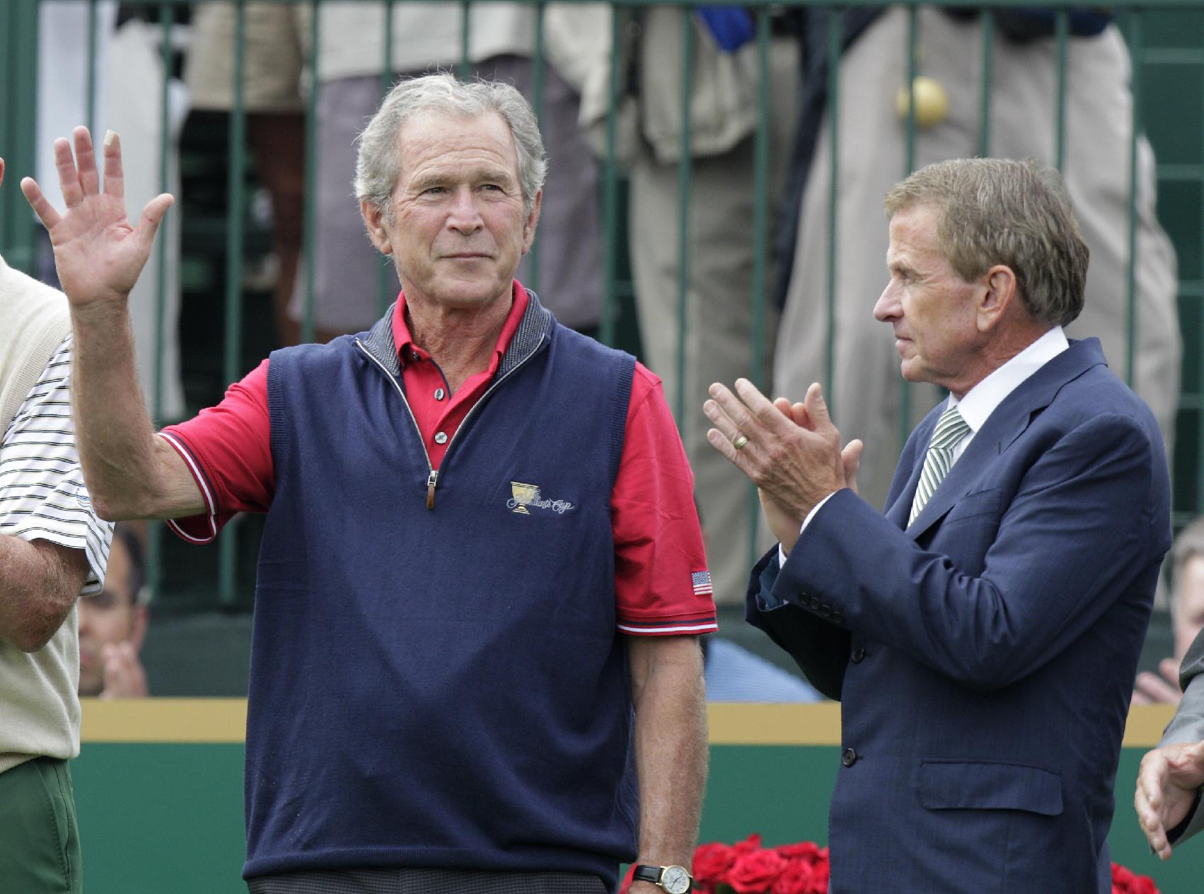 Former President George W. Bush, left, and PGA Tour commissioner Tim Finchem are introduced before the start of the four-ball match at the Presidents Cup golf tournament at Muirfield Village Golf Club Thursday, Oct. 3, 2013, in Dublin, Ohio