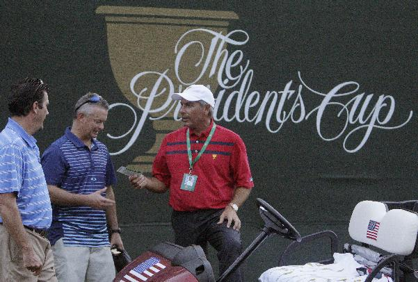 U.S. captain Fred Couples, right, talks with fans after play was called because of darkness during a foursome match at the Presidents Cup golf tournament at Muirfield Village Golf Club on Saturday, Oct. 5, 2013, in Dublin, Ohio