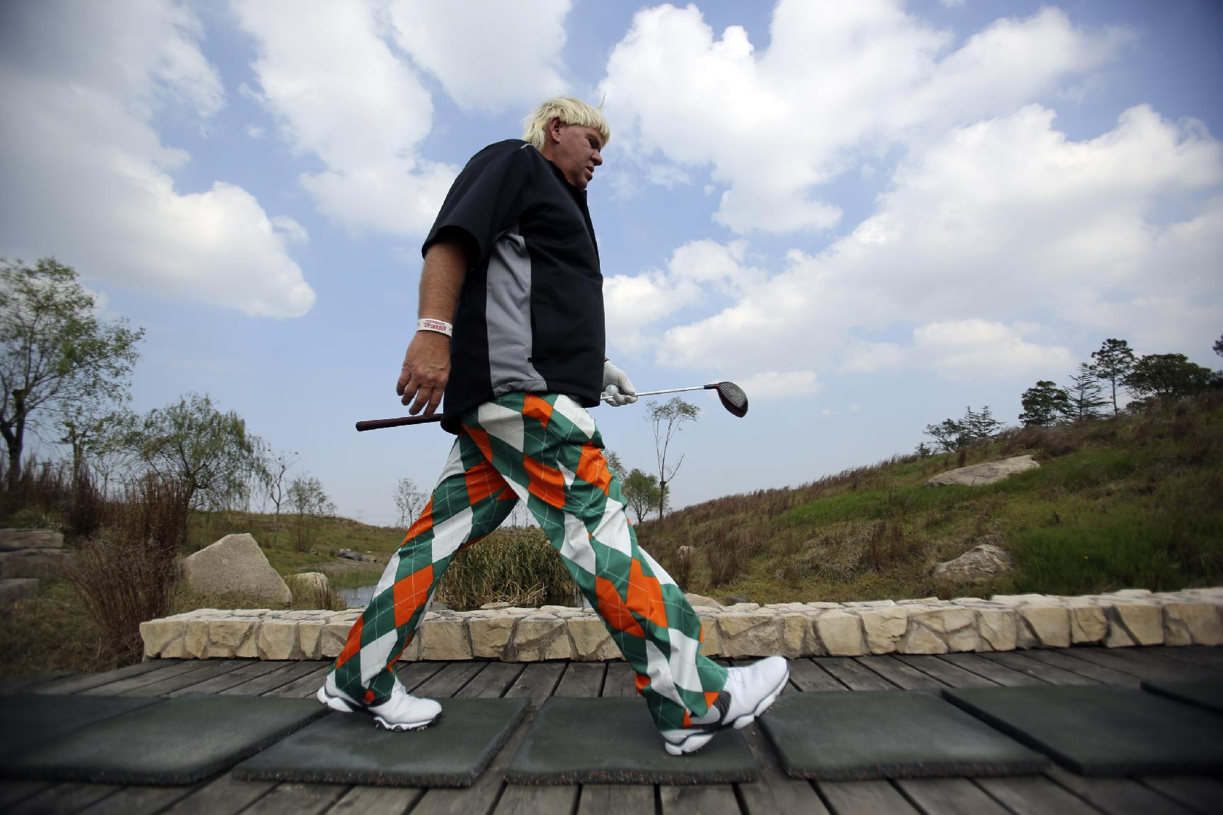 John Daly of the U.S. walks toward to the 3rd hole during a pro-am competition ahead of the BMW Masters golf tournament at the Lake Malaren Golf Club in Shanghai, China, Wednesday, Oct. 23, 2013. The European Tour event will begin on Oct. 24