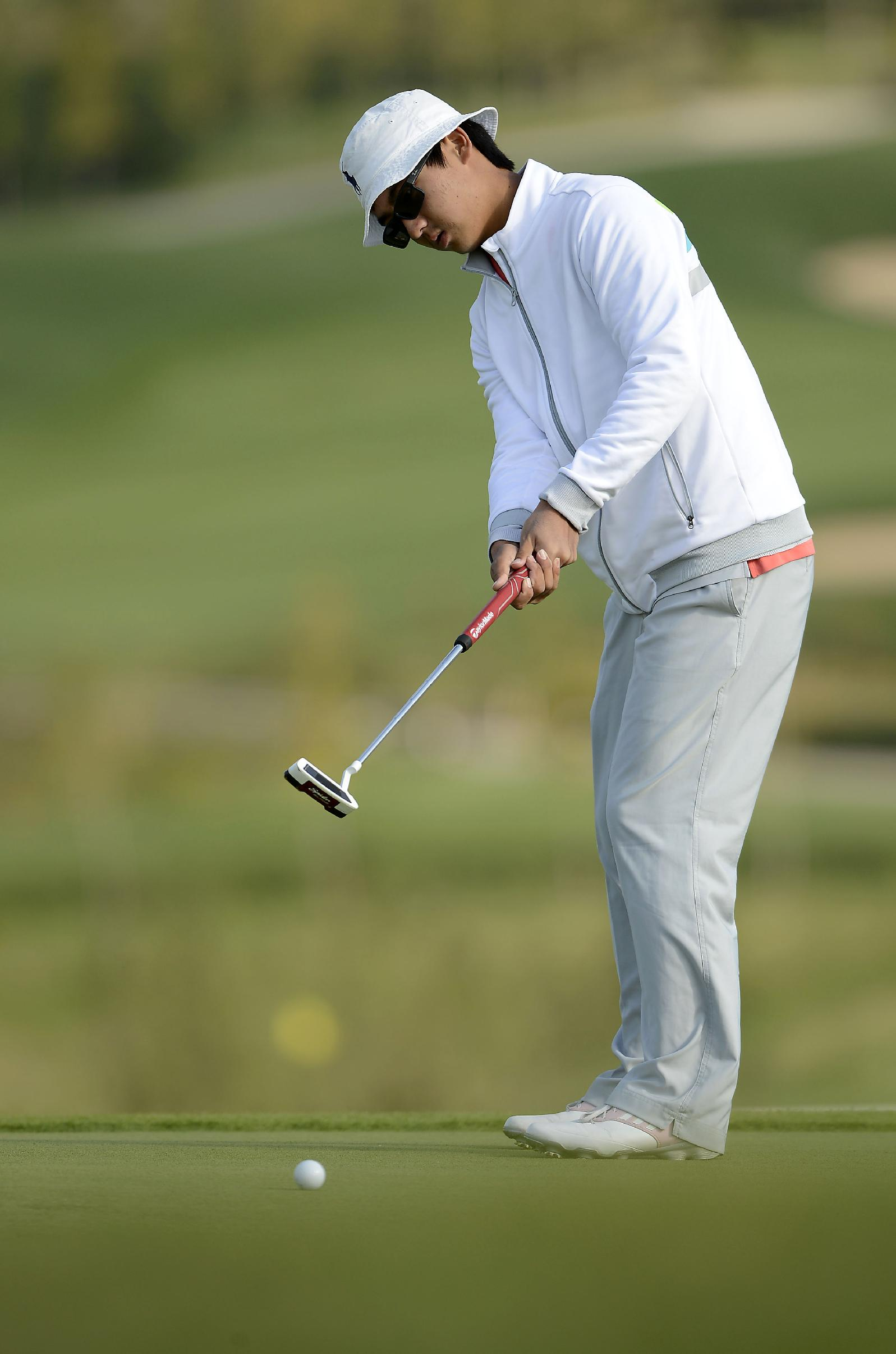 In this photo released by the Asia -Pacific Amateur Championship, Dou Zecheng of China putts during round one of the Asia -Pacific Amateur Championship golf tournament at Nanshan International Golf Club, Garden Course, in Longkou City, China on Thursday, Oct. 24, 2013
