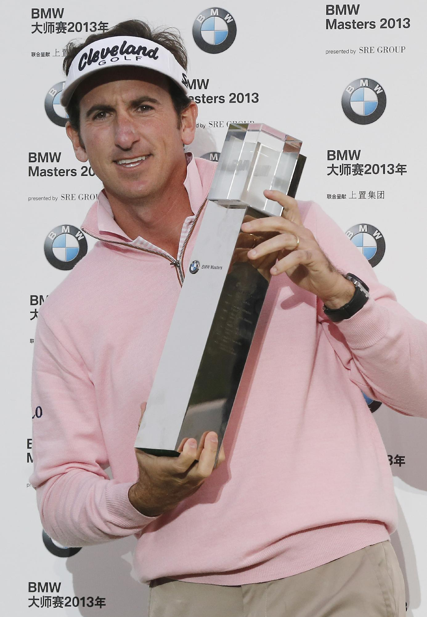 Spain's Gonzalo Fernandez-Castano poses his trophy for photographers during the award ceremony of the BMW Masters golf tournament at the Lake Malaren Golf Club in Shanghai, China, Sunday, Oct. 27, 2013. Fernandez-Castano won the tournament at 11-under 277